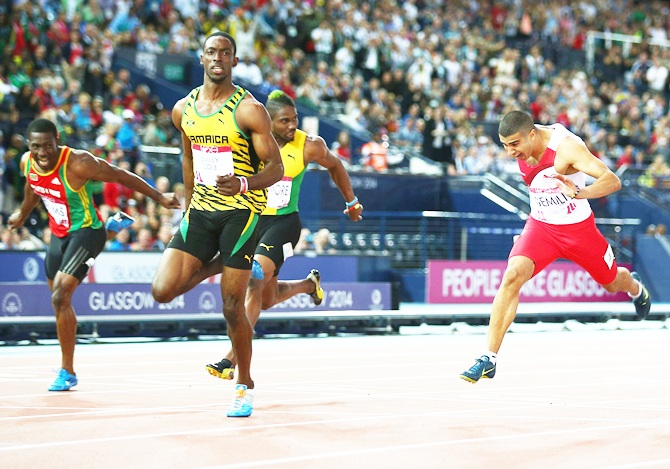 Kemar Bailey-Cole of Jamaica, second right, crosses the line to win gold ahead of silver medalist Adam Gemili of England, right, in the Men's 100 metres final