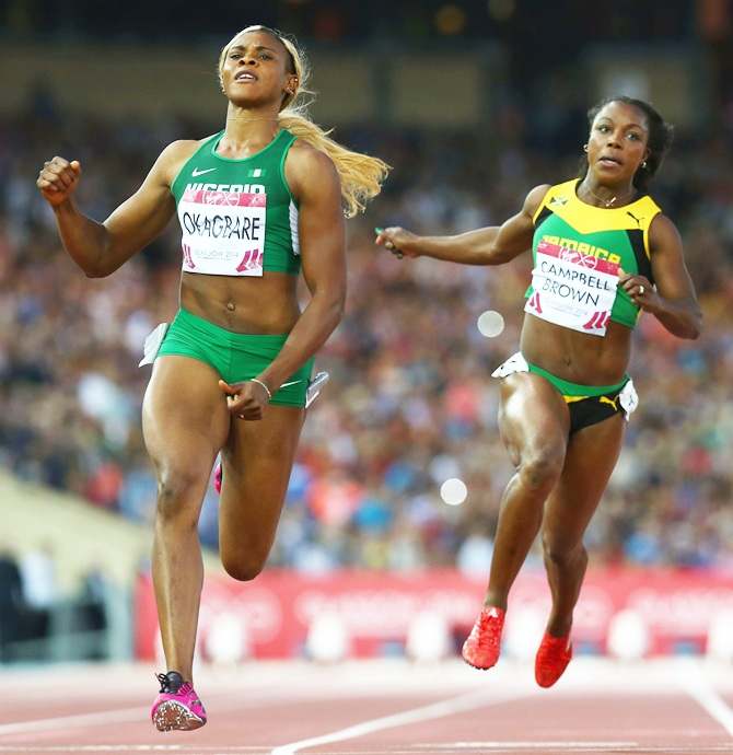 Blessing Okagbare of Nigeria, left, crosses the line to win gold ahead of silver   medalist Veronica Campbell-Brown of Jamaica in the Women's 100 metres final