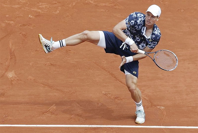 Tomas Berdych of the Czech Republic plays a return against John Isner of the U.S. in their men's singles match at the French Open tennis tournament at the Roland Garros on Sunday