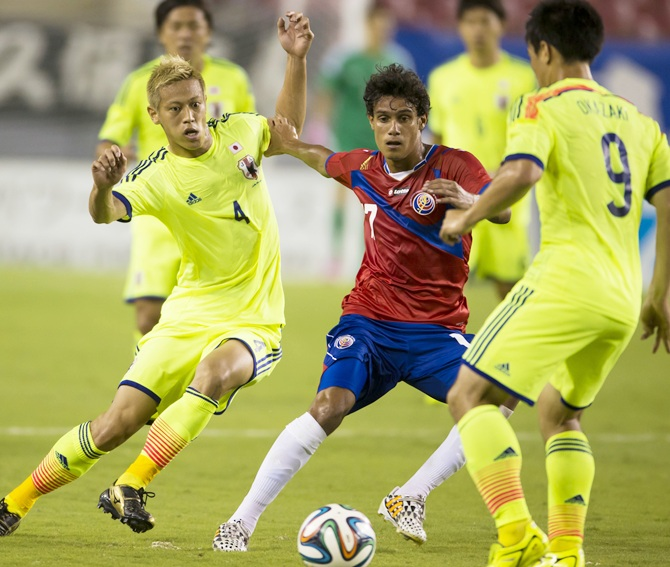 Japan's national soccer team's Keisuke Honda ,left, challenges Costa Rica's Christian Bolanos near Japan's Shinji Okazaki,right, during their international friendly