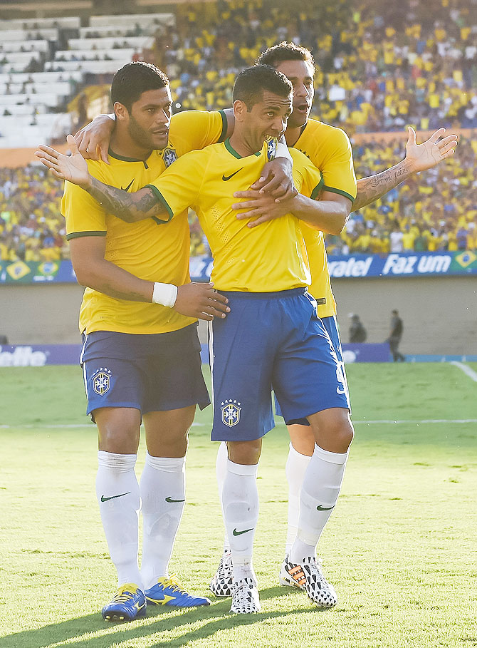 Daniel Alves (centre) of Brazil celebrates with Hulk (left) and Fred after scoring a goal during their international friendly at Serra Dourada Stadium on Tuesday