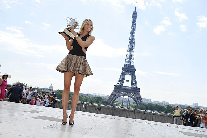 Maria poses with her trophy near the Eiffel Tower in Paris on Sunday