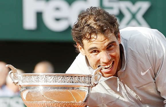 Rafael Nadal of Spain bites the trophy as he poses during the ceremony after defeating Novak Djokovic of Serbia to win the French Open title at the Roland Garros in Paris on Sunday