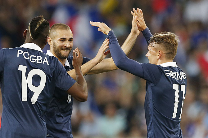 France's Antoine Griezmann (R) celebrates with team mates Paul Pogba (L) and Karim Benzema his goal against Jamaica during their international friendly at Pierre Mauroy Stadium in Villeneuve d'Ascq on Sunday