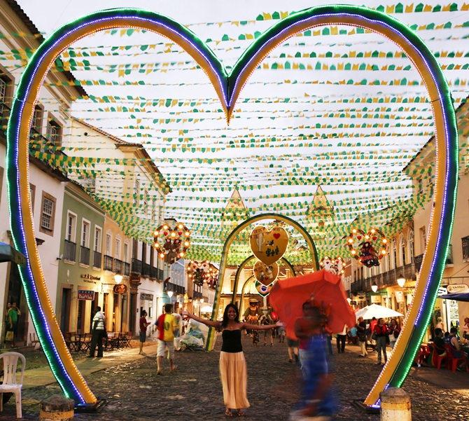 A woman pose for a picture under street decorations on the public square where the fan zone for soccer matches will be held at Pelourinho neigborhood ahead of the 2014 World Cup in Salvador