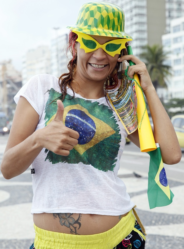 A Brazilian fan gives a thumbs up on Copacabana Beach as the 2014 FIFA World Cup nears