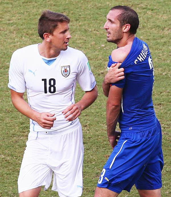Giorgio Chiellini of Italy pulls down his shirt after being bitten by Luis Suarez (not pictured) as Gaston Ramirez of Uruguay looks on