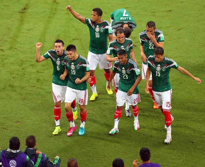Mexico players celebrate a goal against Cameroon