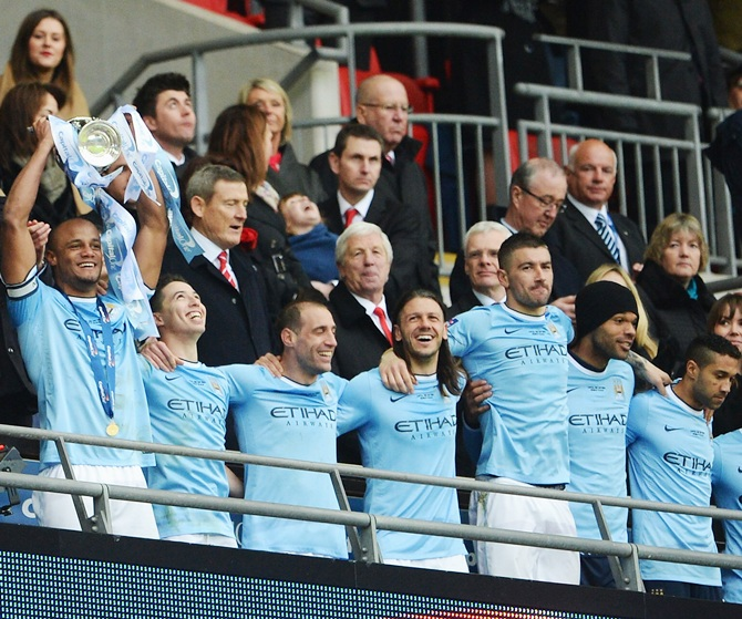 Vincent Kompany of Manchester City lifts the trophy with team mates after the League Cup final against Sunderland at Wembley Stadium.