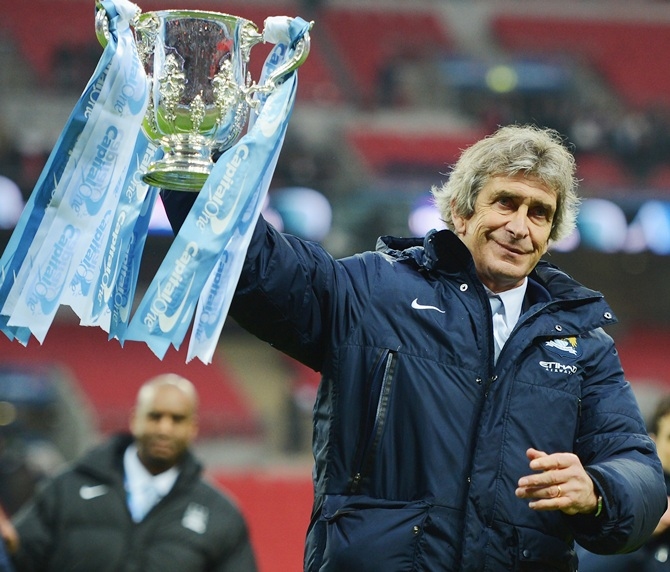 Manuel Pellegrini, manager of Manchester City celebrates victory with the trophy.