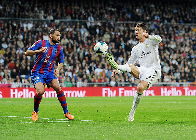 Cristiano Ronaldo (right) of Real Madrid controls the ball as Loukas Vyntra of Levante UD looks on during their La Liga match at Santiago Bernabeu stadium on Sunday