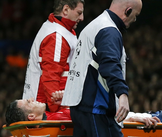 Manchester United's Robin van Persie leaves the pitch on a stretcher