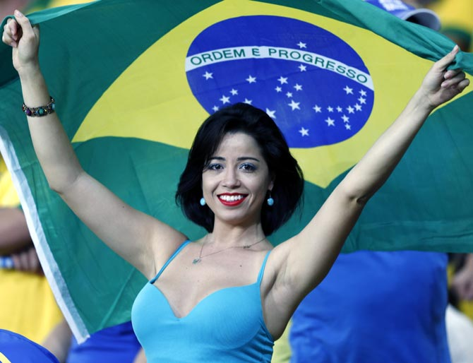 Brazilian football fan cheers for her team.