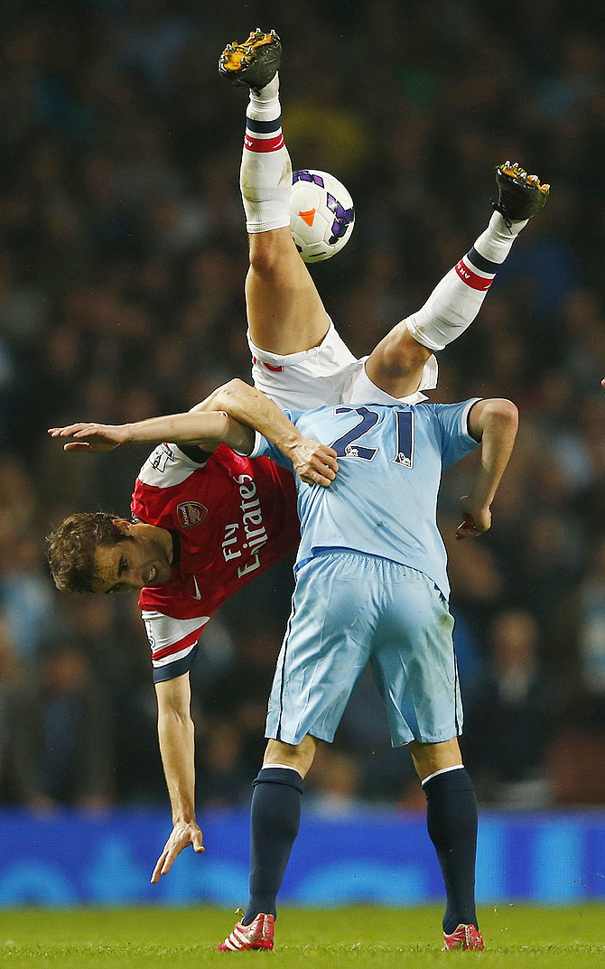 Arsenal's Mathieu Flamini (left) challenges Manchester City's David Silva during their English Premier League match at The Emirates Stadium in London on Saturday