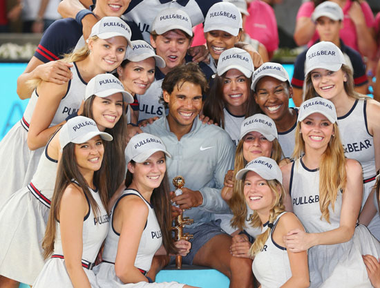 Rafael Nadal of Spain poses for a photograph with his winners trophy and model ball girls after victory in Madrid