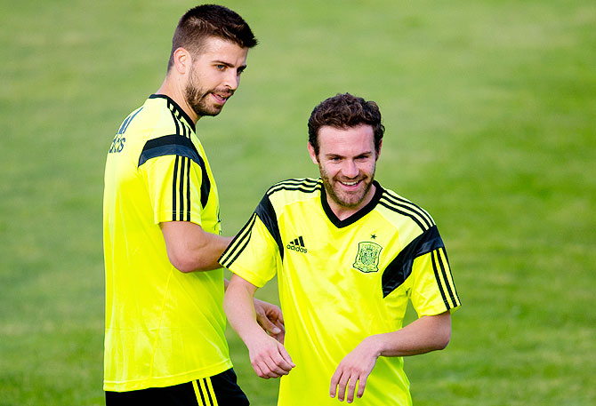 Gerard Pique (left) and Juan Mata of Spain joke during a training sesion.