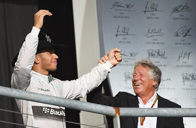 Lewis Hamilton of Great Britain and Mercedes GP celebrates on the podium with former champion Mario Andretti following his victory on Sunday