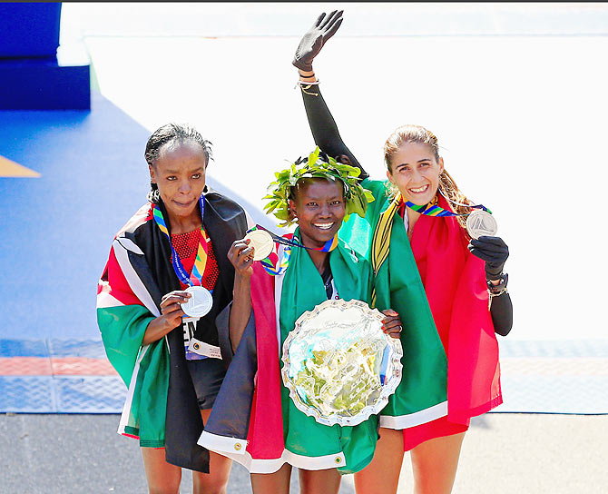 Mary Keitany (centre) of Kenya celebrates with the first place trophy alongside second place Jemima Sumgong (left) of Kenya and third place Sara Moreira (right) of Portugal during the trophy presentation after the New York City Marathon on Sunday