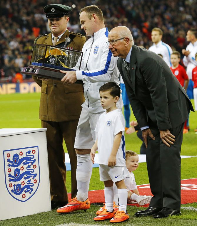 England captain Wayne Rooney stands with his sons Klay (on ground) and Kai after receiving a golden cap from Bobby Charlton (R) to mark his 100th cap