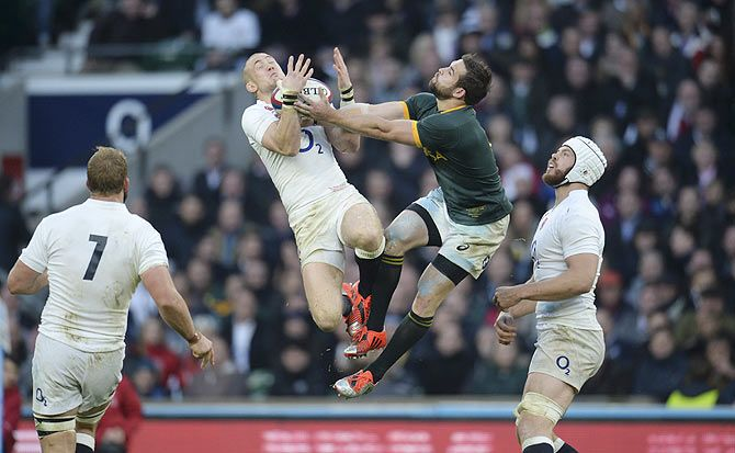 England's Mike Brown (2nd from left) catches the ball despite the attentions of South Africa's Cobus Reinach during their international rugby union match at Twickenham in London on November 15