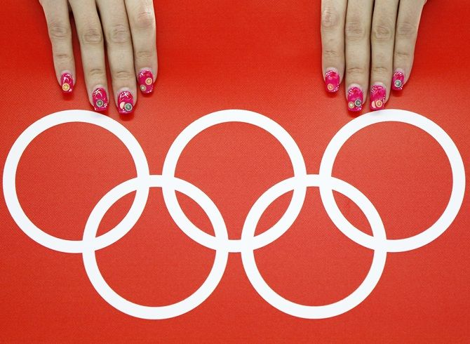 A volunteer's nails are seen beside the Olympic rings