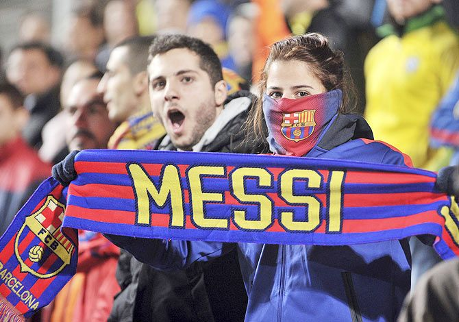 A Barcelona fan holds a scarf with Lionel Messi's name on it during the Champions League Group F soccer match between APOEL Nicosia and Barcelona on Tuesday