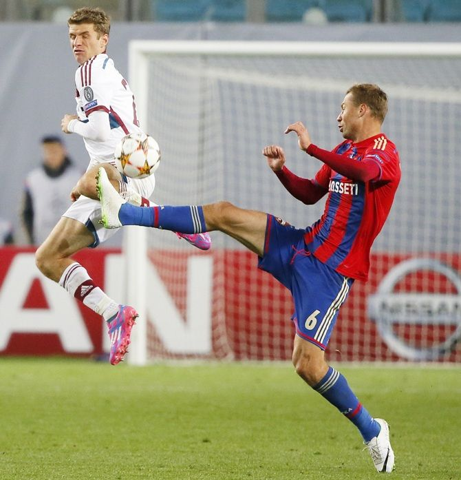 CSKA Moscow's Aleksei Berezutski, right, fights for the ball with Bayern Munich's Thomas Mueller