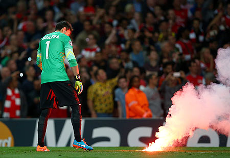 Fernando Muslera of Galatasaray AS carries a flare off the pitch during the UEFA Champions League group D match against Arsenal FC at Emirates Stadium on Tuesday