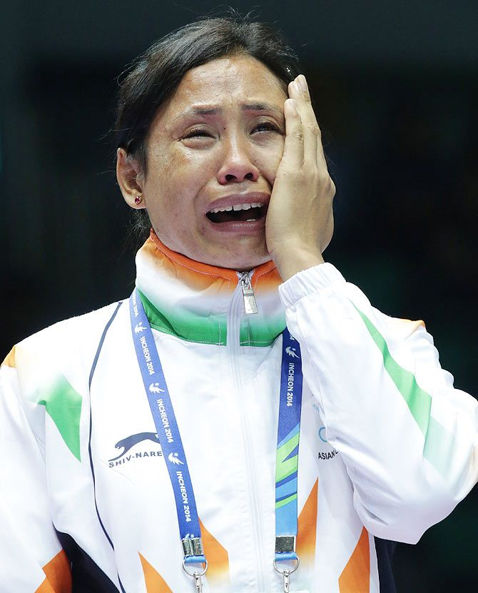 Sarita Devi weeps after she refuses her bronze medal at the Asian Games in Incheon. Photograph: Chung Sung-Jun/Getty Images