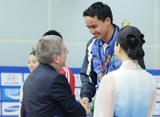 IOC President Thomas Bach presents Rai Jitu of India with his gold medal in the 50m Pistol Men's event at Ongnyeon International Shooting Range