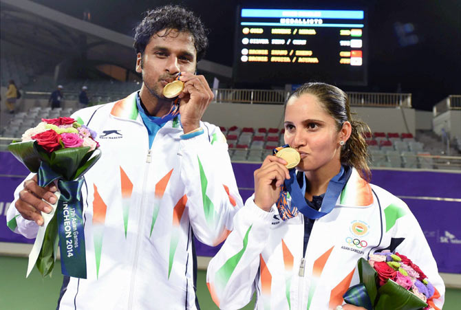 Sania Mirza (right) and Saketh Myneni pose with their gold medals.
