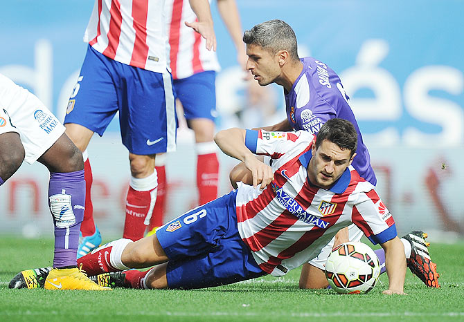 Koke of Club Atletico de Madrid is tackled by Salva Sevilla of RCD Espanyol during their La Liga match at Vicente Calderon Stadium in Madrid on Sunday