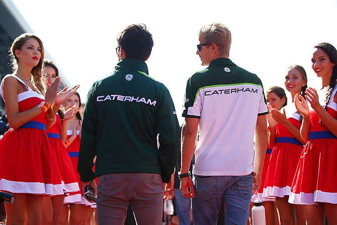 Kamui Kobayashi of Japan and Caterham and Marcus Ericsson of Sweden and Caterham walk out for the drivers' parade before the Russian Formula One Grand Prix at Sochi