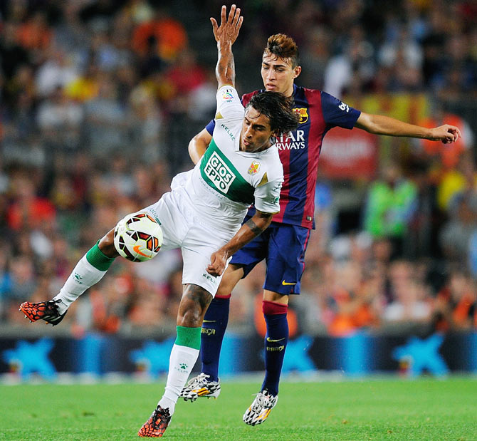 Damian Suarez (left) of Elche FC is challenged by Munir El Haddadi of FC Barcelona during their La Liga match on Sunday