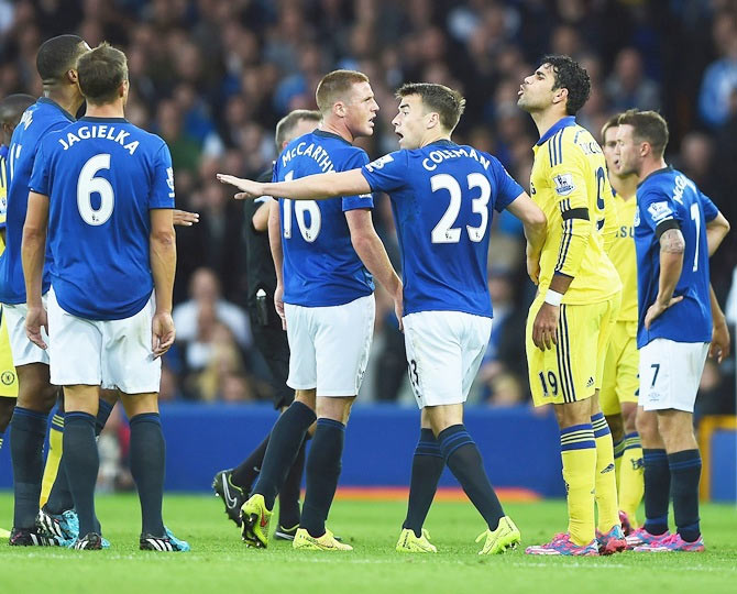 Diego Costa of Chelsea exchanges words with Sylvain Distin of Everton as Seamus Coleman of Everton intervenes during the Barclays Premier League.