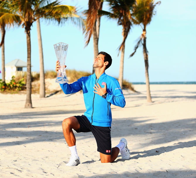 Serbia's Novak Djokovic poses on Crandon Park beach with the Butch Buchholz trophy after his three set victory against Great Britain's Andy Murray in the Miami Open final, in Key Biscayne, Florida, on Sunday