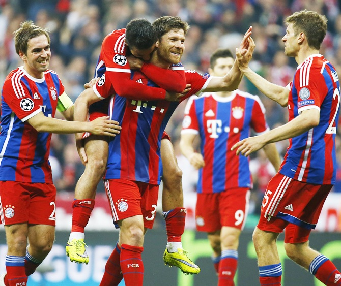 Bayern Munich's Xabi Alonso celebrates with teannates on scoring their sixth goal