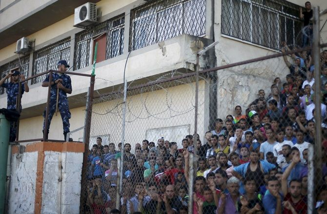 Palestinian spectators are pictured through a fence