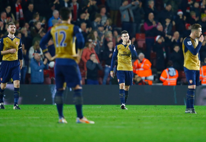 Central defenders Per Mertesacker, left, and Laurent Koscielny of Arsenal, second right, look dejected