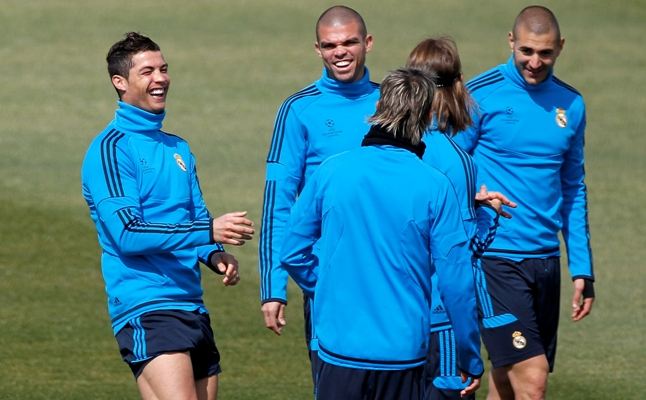 Cristiano Ronaldo (L) smiles beside Pepe (2nd L) and Karim Benzema (R) of Real Madrid CF during a training session
