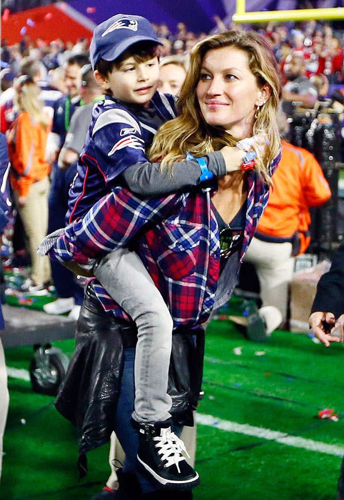 Brazilian supermodel Gisele Bundchen, wife of Tom Brady of the New England Patriots, walks on the field with their son, Benjamin after the Super Bowl XLIX