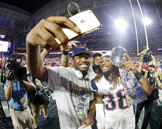 Members of the New England Patriots click a selfie as they celebrate with the Vince Lombardi Trophy after defeating the Seattle Seahawks in Super Bowl XLIX