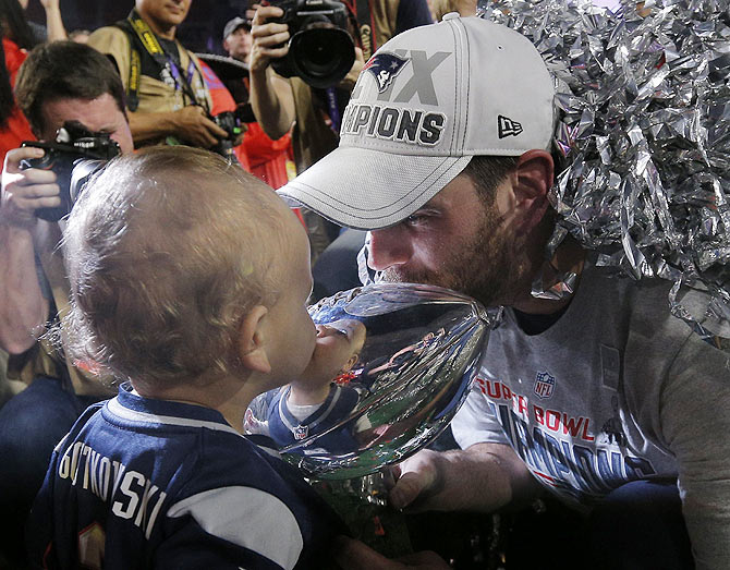 New England Patriots kicker Stephen Gostkowski kisses the Vince Lombardi Trophy with his youngest son after the NFL Super Bowl XLIX football game