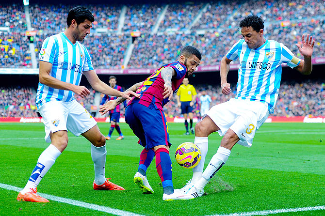 Dani Alves of FC Barcelona fights off a challenge by Welligton Robson (right) and Miguel Torres of Malaga CF during their La Liga match at Camp Nou in Barcelona, on Saturday