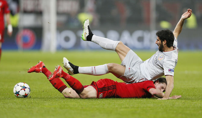 Bayer Leverkusen's Lars Bender goes on the ground after colliding with Atletico Madrid's Raul Garcia (top)
