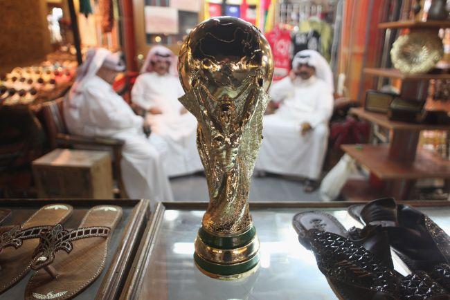 Arab men sit at a shoemaker's stall with a replica of the FIFA World Cup trophy