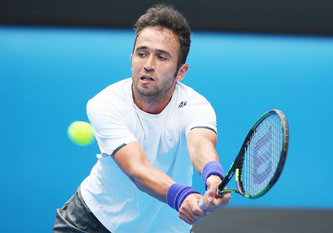 Marsel Ilhan plays a backhand in his first round match against Stanislas Wawrinka