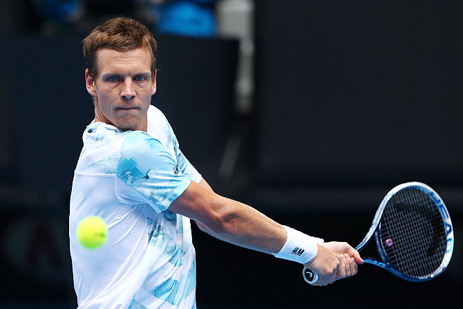 Tomas Berdych of the Czech Republic plays a backhand in his quarter-final against Rafael Nadal of Spain