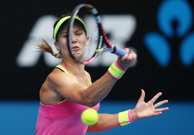 Eugenie Bouchard of Canada plays a forehand against Maria Sharapova of Russia