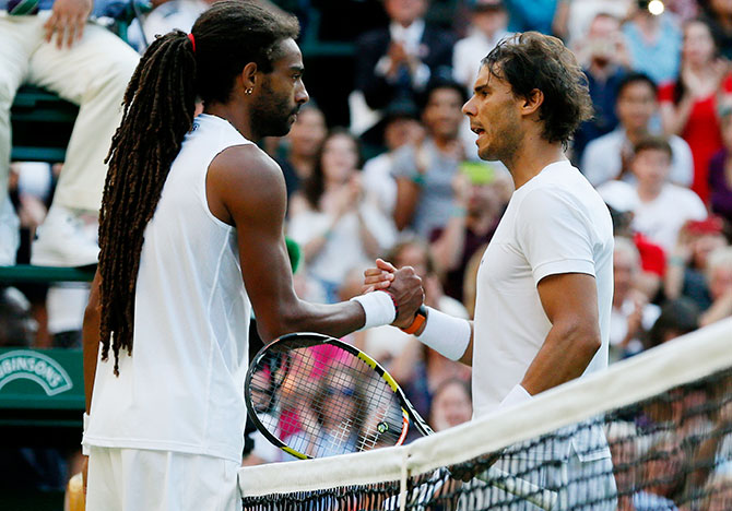 Dustin Brown of Germany shakes hands with Rafael Nadal of Spain